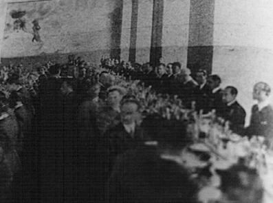 """Fotografia pubblicata su una rivista d'epoca (1932), I transoceanici alla «mensa unica» del nuovo Ministero dell'Aeronautica. Nella parete di fondo è visibile un particolare del murale coloniale – Fonte: """"M.A. de Caterina, Marcello Dudovich: le decorazioni murali (1906 - 1947)""""."""