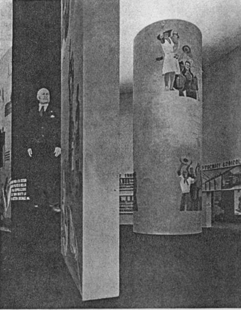 """Foto pubblicata su una rivista d'epoca (1935), Il salone circolare alla IV Mostra Nazionale dell'Agricoltura (Bologna, 12 maggio - 30 giugno 1935). La didascalia della rivista riporta: """"Arch. Nizzoli, pittore Dudovich - Il grande salone circolare"""" - Fonte: """"M.A. de Caterina, Marcello Dudovich: le decorazioni murali (1906 - 1947)""""."""